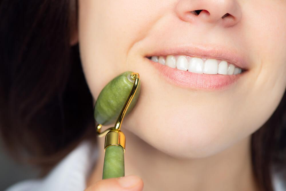 Woman using jade roller on face