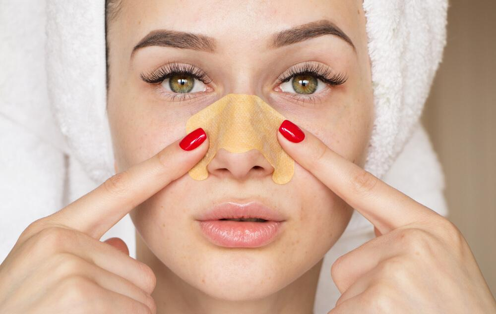 Woman using pore strips on nose