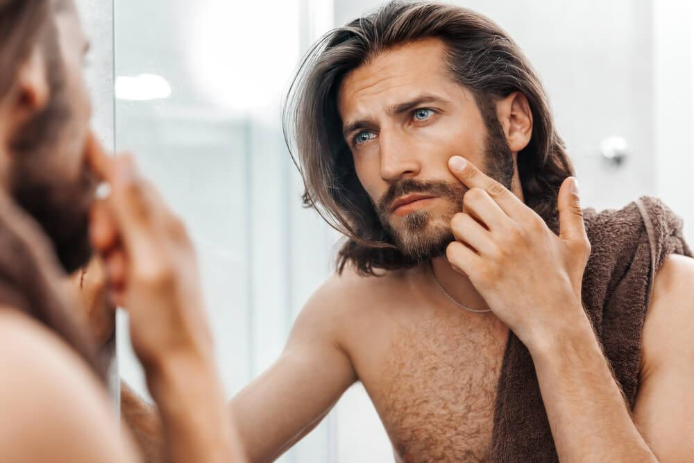 Man looking at skin in mirror