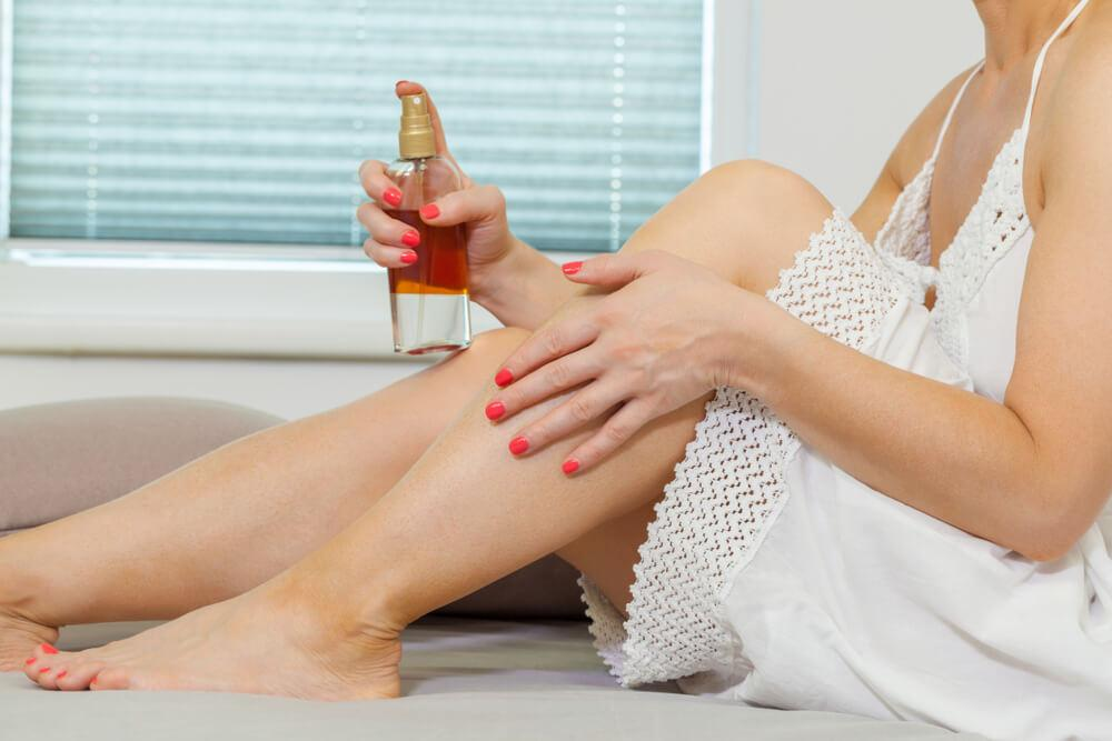 Woman using tanning lotion on leg