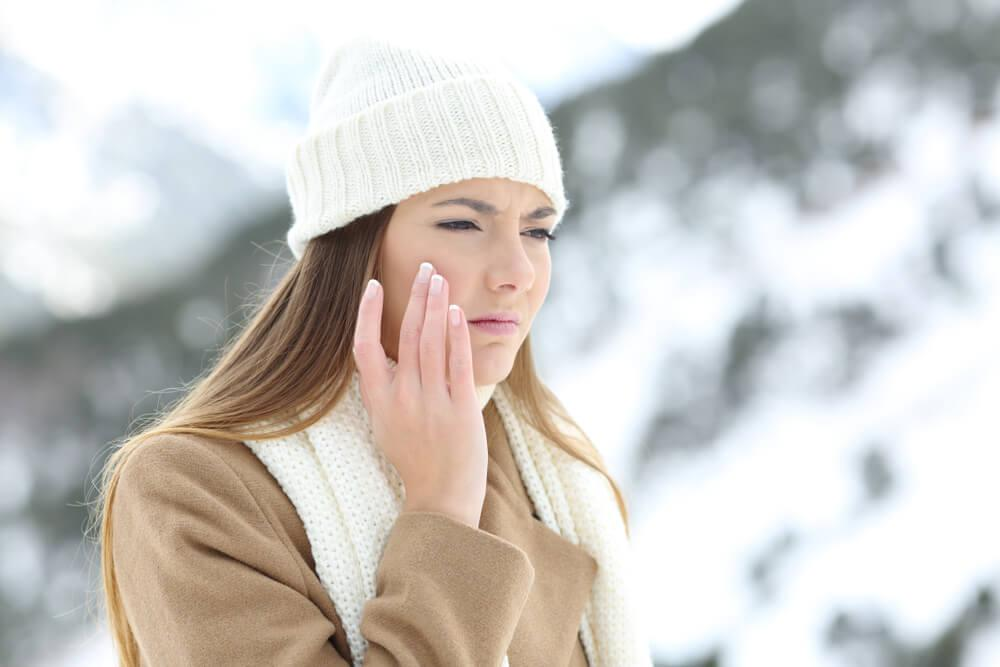 Woman outdoors in winter touching her face